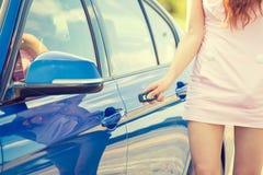 A mulher que as imprensas se abotoam no controlo a distância do carro destrava o sistema de alarme da porta Fotografia de Stock