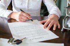 Mulher que assina um contrato de compra do carro Foto de Stock