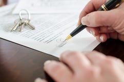 Mulher que assina um contrato dos bens imobiliários Imagens de Stock Royalty Free