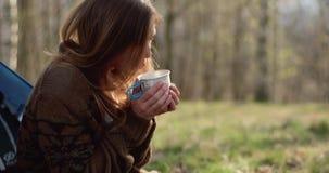 A mulher que bebe a bebida quente gosta do chá ou do café Férias exteriores da barraca de acampamento dos povos dos amigos reais  vídeos de arquivo