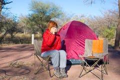 Mulher que bebe a caneca de café quente ao relaxar no local de acampamento Barraca, cadeiras e engrenagens de acampamento Ativida Imagens de Stock