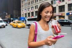Mulher que bebe o suco saudável usando o app do telefone fotografia de stock