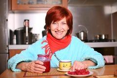 Mulher que bebe um copo do chá com atolamento de framboesa Imagens de Stock