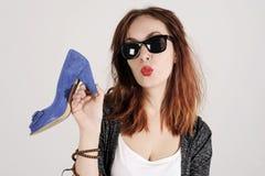 Mulher que beija e que guarda uma sapata Conceito das sapatas dos amores das mulheres Menina da forma e sapatas azuis dos saltos  Fotos de Stock Royalty Free
