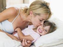 Mulher que beija a rapariga no sorriso da cama Imagem de Stock