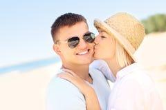 Mulher que beija um homem na praia imagem de stock