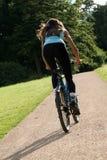 Mulher que biking na estrada Fotos de Stock Royalty Free