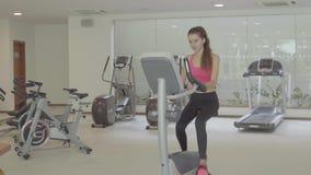 A mulher que biking no gym, exercitando os pés que fazem o cardio- ciclismo de treinamento bikes filme