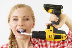 Mulher que burshing seus dentes usando a broca foto de stock