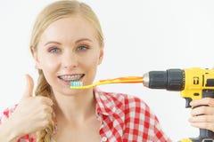 Mulher que burshing seus dentes usando a broca fotografia de stock royalty free