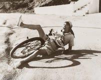 Mulher que cai fora sua bicicleta no lado da estrada fotos de stock royalty free