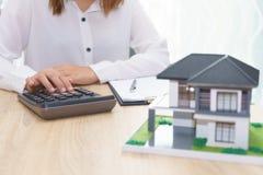 A mulher que calcula sobre o preço da prestação com empréstimo da propriedade concorda imagem de stock