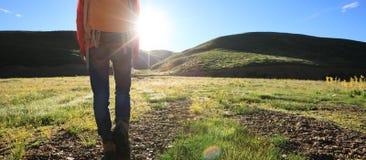 Mulher que caminha em montanhas do nascer do sol Imagens de Stock