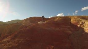 Mulher que caminha ir acima ao pico de montanha vermelho vídeos de arquivo