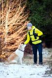 Mulher que caminha na floresta do inverno com cão Imagens de Stock
