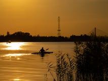 Mulher que canoeing no por do sol em Vistula River, Polônia Cenário e cores surpreendentes fotos de stock