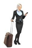 Mulher que carreg uma mala de viagem e uma escrita sms Fotografia de Stock Royalty Free