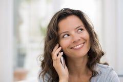 Mulher que chama com telefone celular interna Foto de Stock Royalty Free