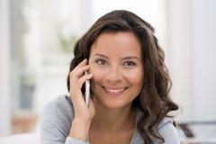 Mulher que chama com telefone celular interna Fotografia de Stock