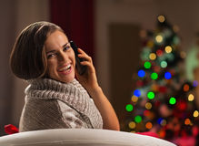 Mulher que chama o móbil na frente da árvore de Natal Fotografia de Stock