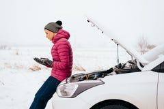 Mulher que chama para a ajuda ou o auxílio - divisão do carro do inverno Imagem de Stock