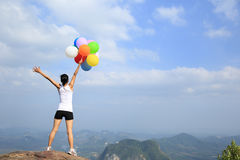 Mulher que cheering no pico de montanha com balões coloridos Foto de Stock
