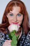 A mulher que cheira uma rosa imagens de stock royalty free