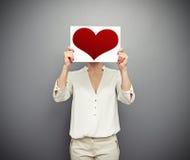 Mulher que cobre sua cara com o coração vermelho Fotos de Stock Royalty Free