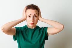 Mulher que cobre suas orelhas isoladas em um fundo branco olhando a câmera fotos de stock