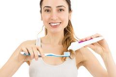 Mulher que cola o dentífrico ao teethbrush foto de stock royalty free