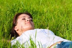 A mulher que coloca em um gramado e está sonhando Fotografia de Stock Royalty Free