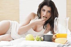 Mulher que coloca na cama e que come o pequeno almoço Fotografia de Stock Royalty Free