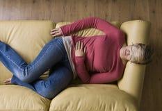 Mulher que coloca na máscara desgastando do sono do sofá Fotografia de Stock