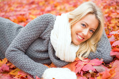 Mulher que coloca nas folhas vermelhas e no sorriso Fotografia de Stock Royalty Free