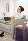 Mulher que coloca no sofá e que usa o portátil. Vista traseira Imagens de Stock Royalty Free