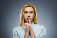 Mulher que coloca o dedo nos bordos que pedem shh, silêncio, silêncio no fundo cinzento imagem de stock