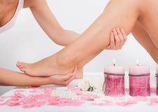 Mulher que começ a massagem dos pés Fotos de Stock Royalty Free