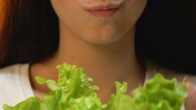 Mulher que come a alface fresca e que sorri, dieta do vegetariano, evitando refeições de carne video estoque