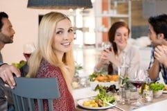 Mulher que come com seus amigos Imagem de Stock