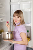 Mulher que come da bandeja perto do refrigerador Imagens de Stock