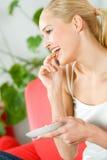 Mulher que come e que presta atenção à tevê Imagem de Stock Royalty Free