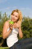Mulher que come a maçã verde no glade do verão imagens de stock