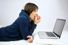 Mulher que come a maçã vermelha na frente do computador Fotografia de Stock