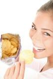 Mulher que come microplaquetas Imagens de Stock Royalty Free