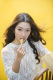 Mulher que come microplaquetas de batata Fotos de Stock