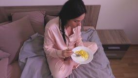 Mulher que come na cama vídeos de arquivo