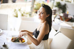 Mulher que come no restaurante foto de stock royalty free