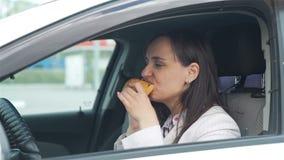 Mulher que come o almoço e que usa o telefone celular no carro video estoque
