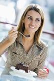 Mulher que come o bolo de chocolate no café Foto de Stock