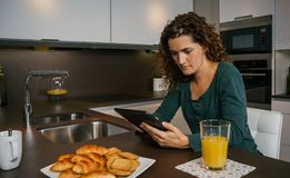 Mulher que come o café da manhã e que olha a tabuleta imagem de stock royalty free